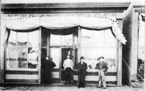 Carrie Ingalls, far left, stands in the doorway of the De Smet Leader where she worked as a typesetter.
